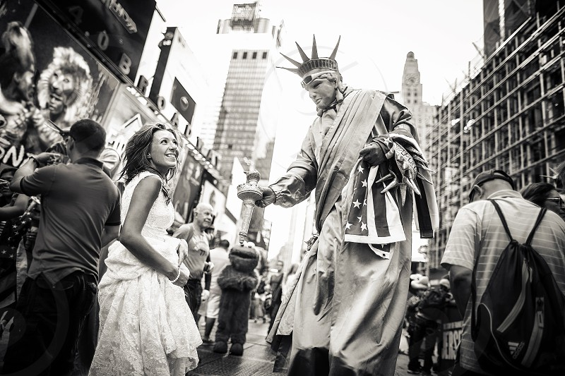 A young bride reacts to a stilt-walking Statue of Liberty performer in Times Square. photo