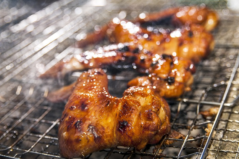 Closeup of chicken wings barbecue on grill. Shallow depth of field. photo