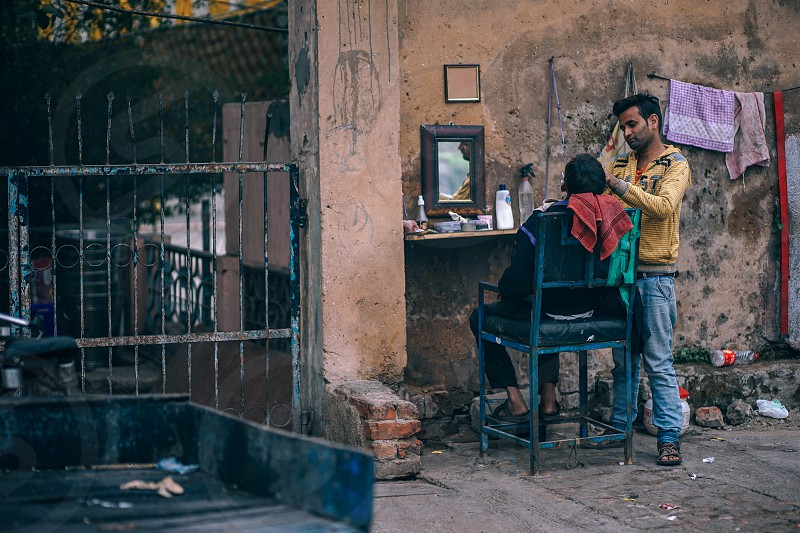 A wall a mirror and a chair is about all a barber needs to take care of his customers photo