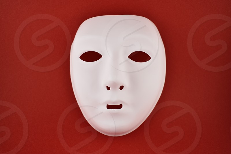 Plastic white face mask. White mask on a red background. Plastic human mask photo