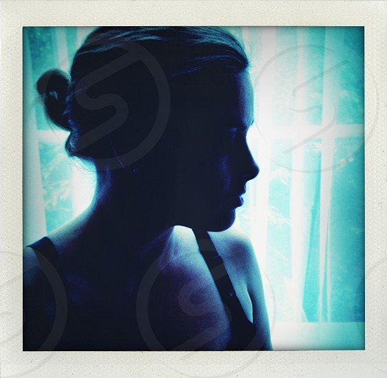 Silhouette of a woman in front of a window photo