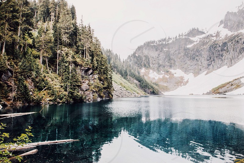 blue lake water and snow covered mountain photo
