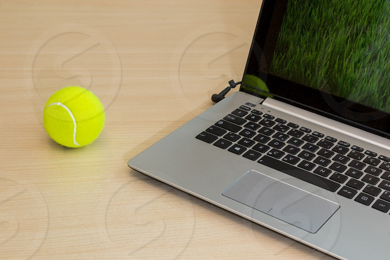 Wimbledon is coming and so people will watch it or follow it on their laptop at work or home or on holidays. This photo illustrates this a laptop and a tennis ball on desk. photo
