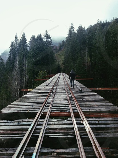 man walking on elevated train track platform in black hooded coat in mountains photo
