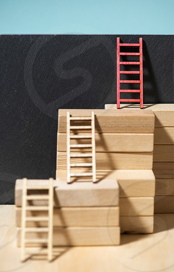 Ladders on the wall. Concept for success and growth. Stairs made of wooden blocks. Blue wall.  photo