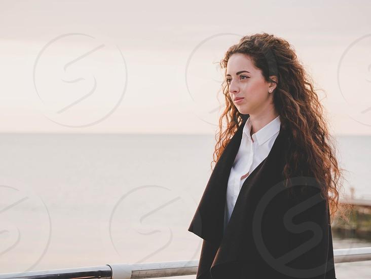 Beautiful girl with curly long hair towards the camera on sunny spring sea beach. Young stylish business woman in fashion black coat and white shirt near ocean. photo
