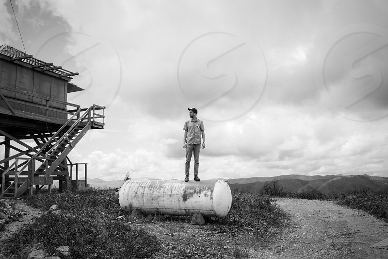 man standing on white water tank during daytime photo