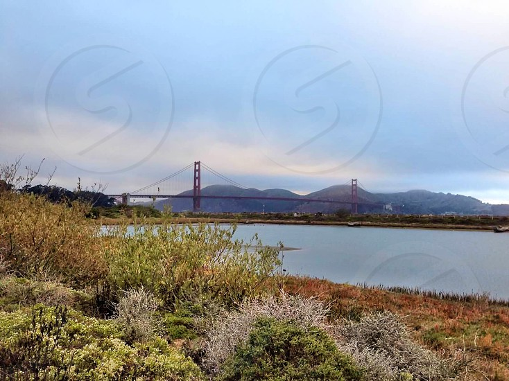 san francisco golden gate bridge with over looking view of mountains under nimbus clouds photo