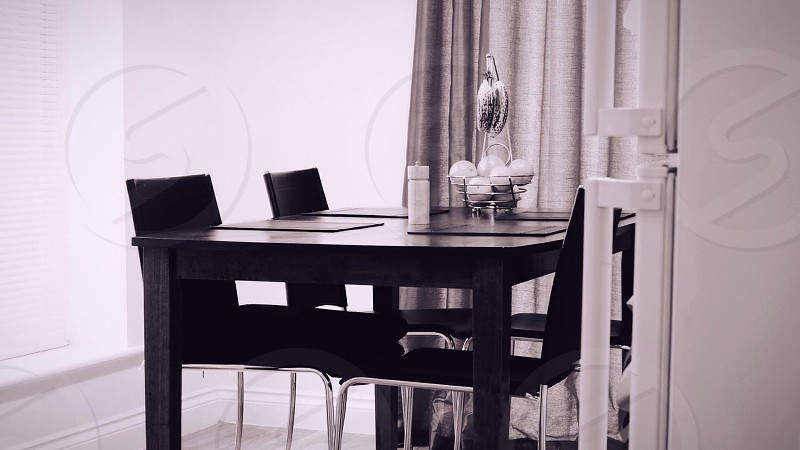 wooden dining table with 4 dining chairs greyscale photography photo