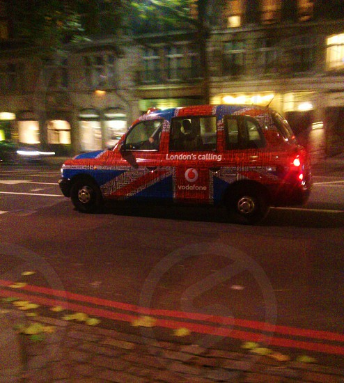 red and blue london's calling vodafone cab photo