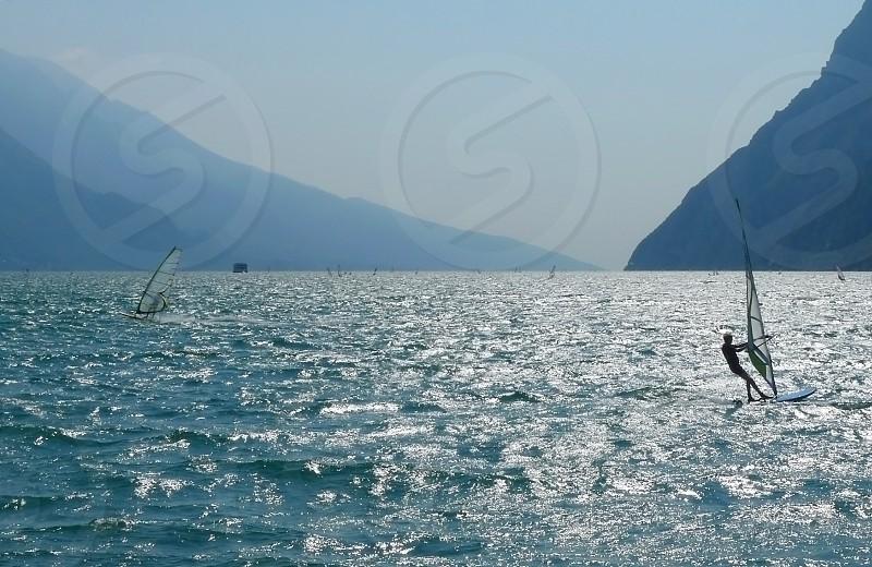 windsurfing on Lake Garda. Italy. torbole. riva. wind. watersports. windsurfing spot. backlight. sunshine on water. silver. water. mountains. travel. vacation. summer. mediterranean. blue photo