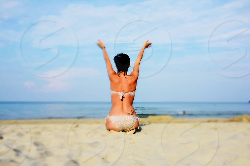 Woman in bikini with a tattoo on her back spreading her arms towards sea on a beach photo