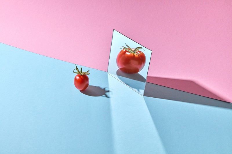 A small red tomato with a green stem is reflected large in a mirror on a blue-pink background with copy space. photo