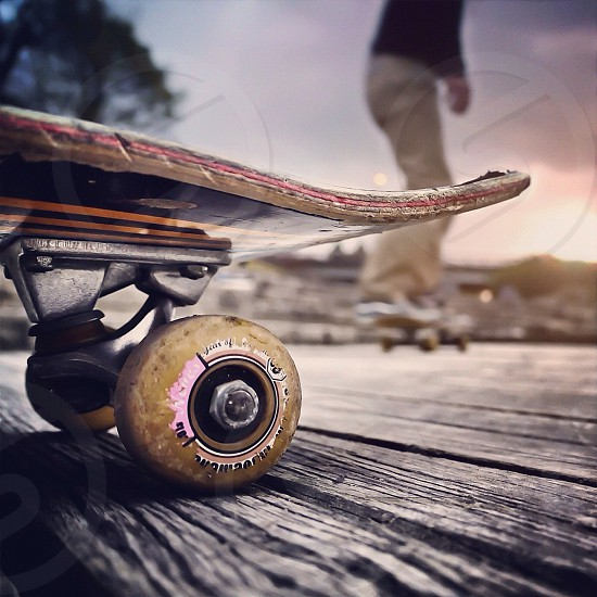 view of black skateboard with yellow wheel photo