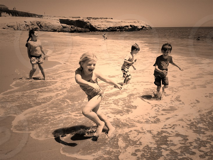 4 children playing in the sea shore photo