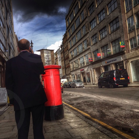 man standing facing the red bollards  photo