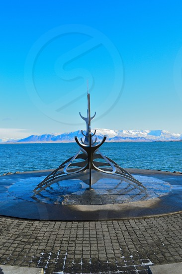 metal sculpture by water photo