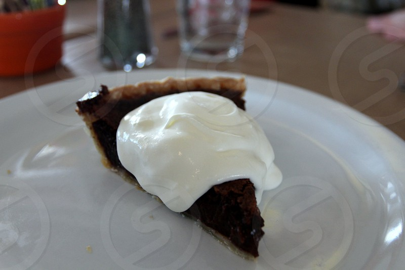 Chocolate chess pie with dollop of hand whipped cream on white plate photo