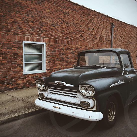 black vintage pick up truck near brick wall photo