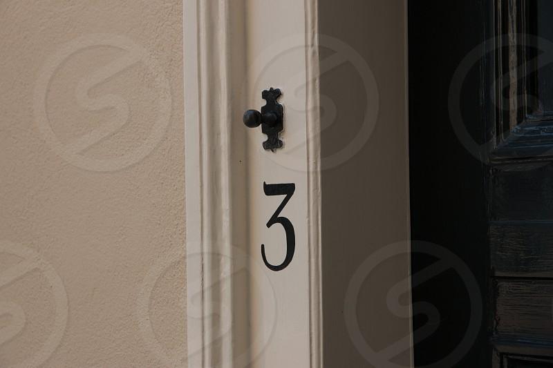 """Number """"three""""  with antique doorbell on a door post photo"""