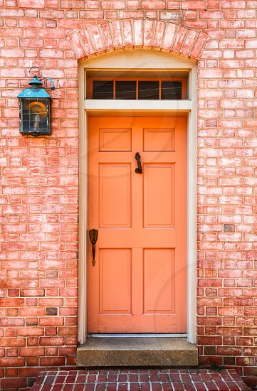 Coral colored door and bricks photo