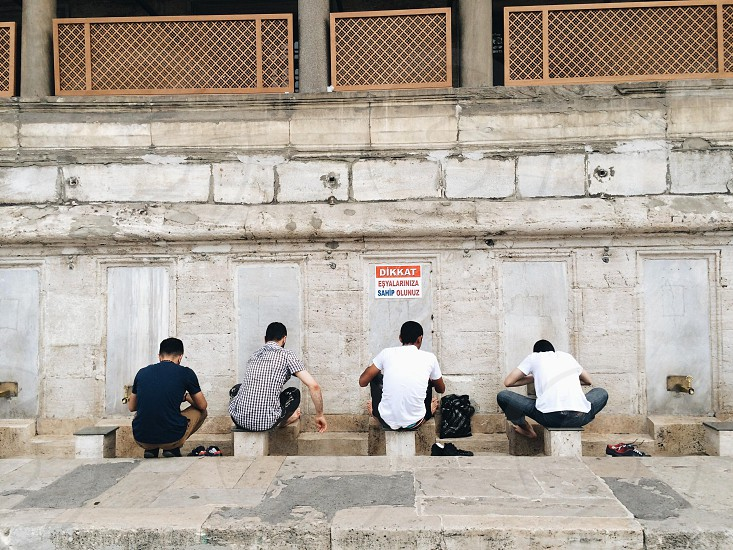 Four men perform ablutions at the Suleimaniye Mosque in Istanbul Turkey   photo