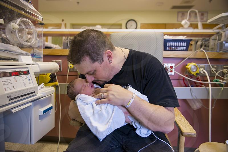 Dad holding newborn infant in NICU photo