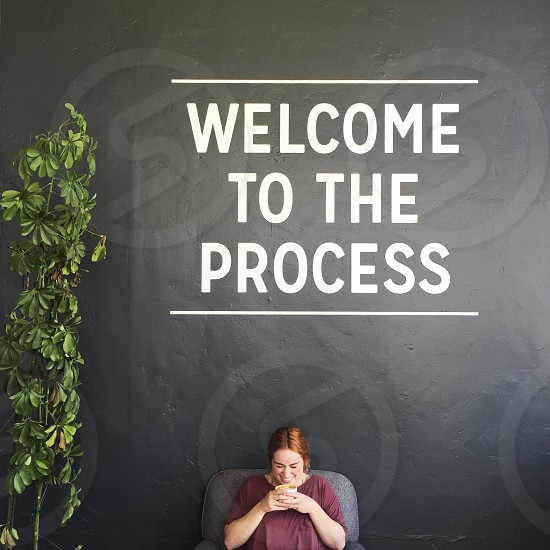 welcome to the process sign on grey concrete wall photo