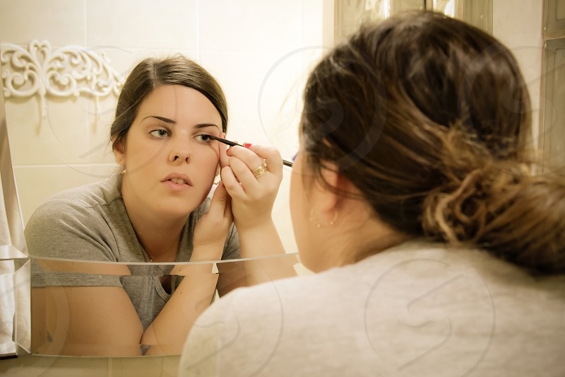 Woman put eyeliner in front of a mirror photo