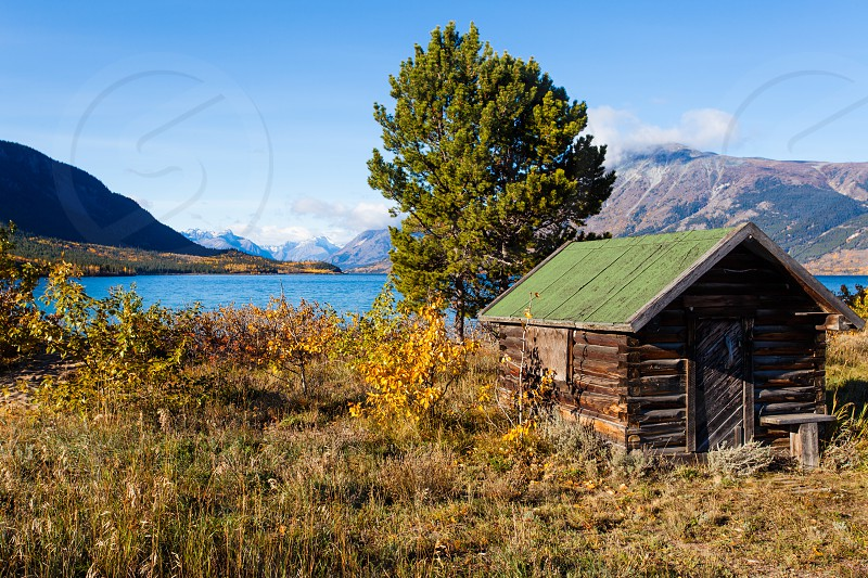 Pristine wilderness Landscape with historic wooden log building at shore of Lake Bennett near Carcross Yukon Territory Canada photo