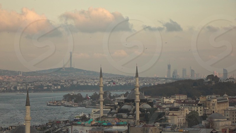 Panoramic view old sity to Rustem Pasha Mosque at Eminonu Istanbul Bosphorus strait with travel ships and boards and flying bird on a background cloudy sky. Slow motion Full HD video 240fps 1080p. photo