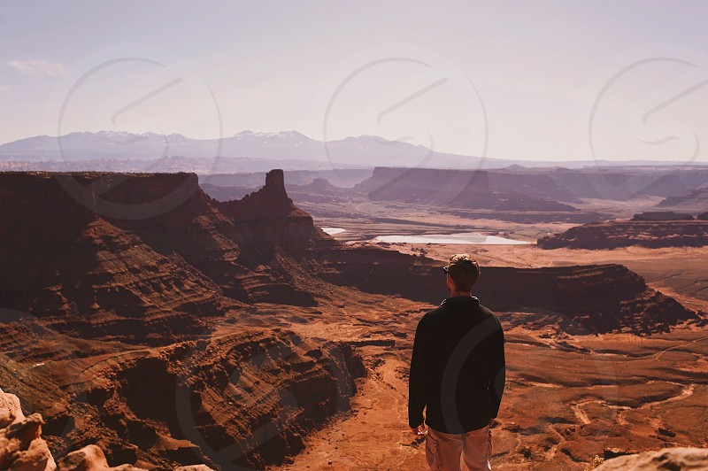 man in black long sleeve shirt standing on high ground while looking to the plateau during daytime photo