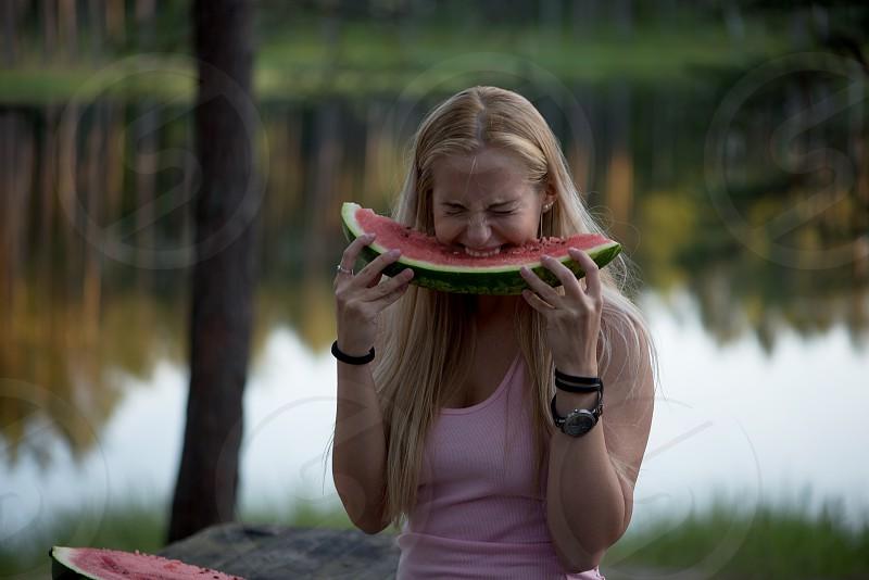 Beautiful young woman eating watermelon photo