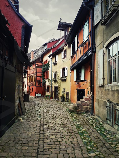 Narrow streets of the old Eguisheim village with half-timbered medieval houses along the famous wine route in Alsace France. photo