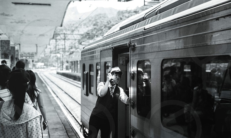 grayscale photo of train man near open door of train in train station at daytime photo