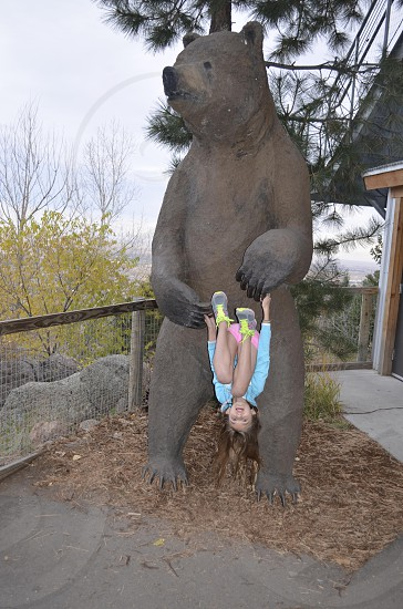 girl in blue hanging upside down from brown bear sculpture outside photo