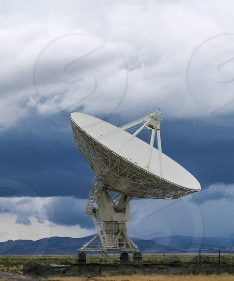 The Karl G. Jansky Very Large Array or VLA radio telescope antenna on the Plains of Agustin in west central New Mexico a powerful astronomy and astrophysics research facility under a stormy summer sky photo