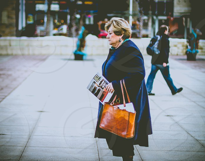 woman in black winter coat with burnished leather tote walking on sidewalk with magazine photo