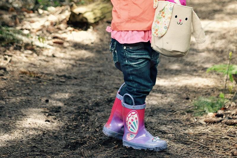 Easter egg hunt bunny basket. Child girl rubber boots trail Spring  photo