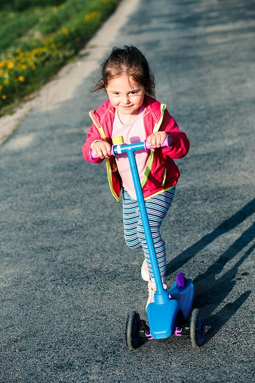 Little adorable girl having fun riding on scooter playing outdoors photo