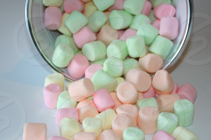 Pastel colored marshmallows spilling out of a white bucket. photo