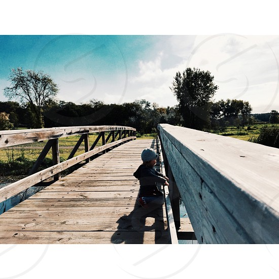 toddler wearing gray beanie cap knees on beige wooden bridge during daytime photo