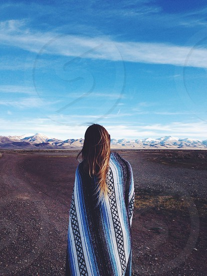 Girl wrapped in blanket in front of mountains.  photo