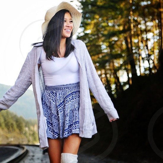 woman in grey scoop neck shirt and blue and white floral skirt with grey cardigan walking on train tracks during daytime photo