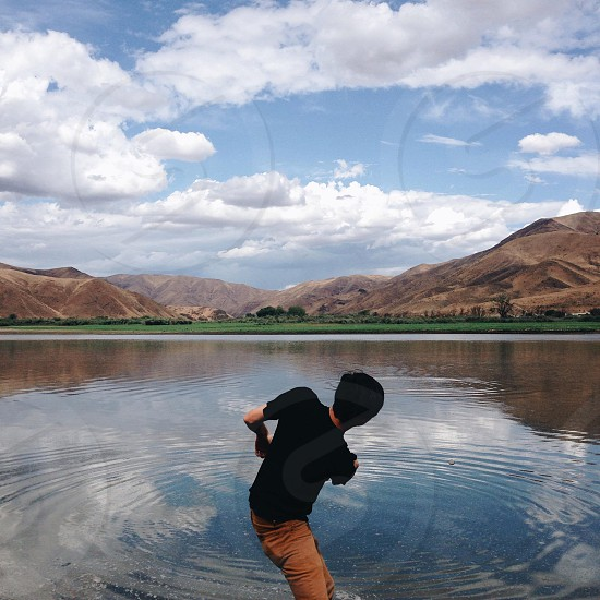 man in black t shirt and brown pants on lake photo