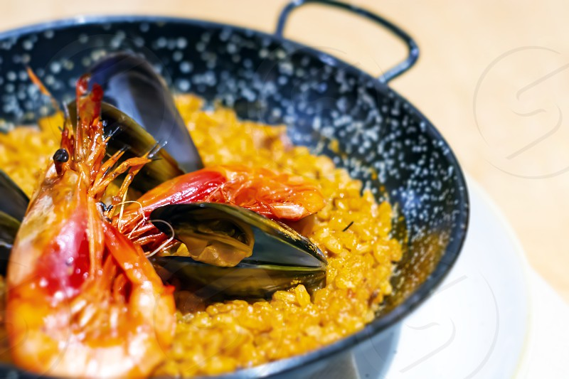 Paella with mariscos in a black pan a typical dish of traditional Spanish cuisine based on seafood and rice. Traditional cuisine photo