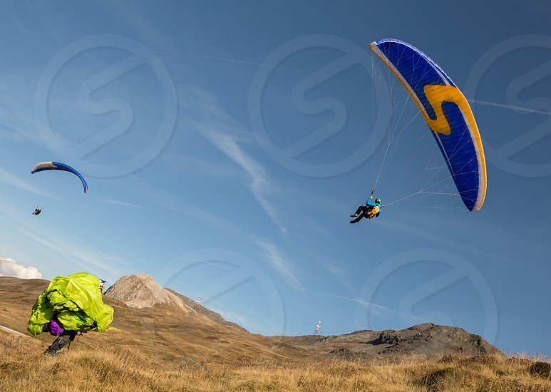 2 paragliders on flight over grassy hill under blue sky photo