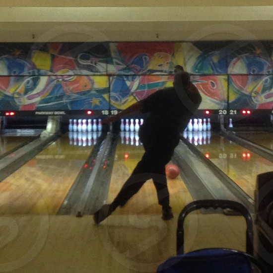 view of a man playing bowling photo