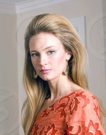 woman in orange damask one shoulder top wearing gold dangling earrings in tilt shift lens photo