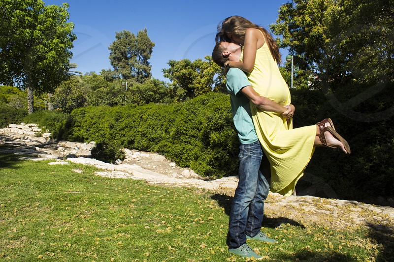 man carrying woman in yellow spaghetti strap dress on green grass lawn during daytime photo